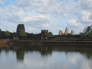"""The big daddy: Angkor Wat. There is a gigantic moat around the entire complex; a stone """"Rainbow Bridge"""" leads in from the west (just visible on the left). Angkor is distinctive, in fact, for facing west rather than east; there is no consensus as to why this was done, though there are several theories."""