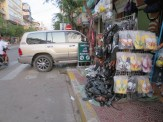 """There's much to admire in this photo. The SUV parked nonchalantly into the street, the disappearance of the sidewalk beneath a shoe """"display,"""" etc. Walking around Phnom Penh is a bit of a challenge."""