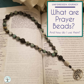 "Set of protestant prayer beads in Jade with black lava beadsand a tree of life charm laid on topof an open bible with text overlay that reads ""Personal Faith: What are protesant prayer beads? And how do I use them?"""