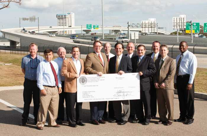 Members from the FDOT and UNF pose in front of the I-95/I-10 interchange in downtown Jacksonville with a $10,000 check donated to the university's engineering college.