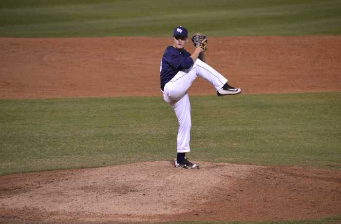 Freshman Austin Drury winds up to deliver a pitch.  Photo by Emily Woodbury