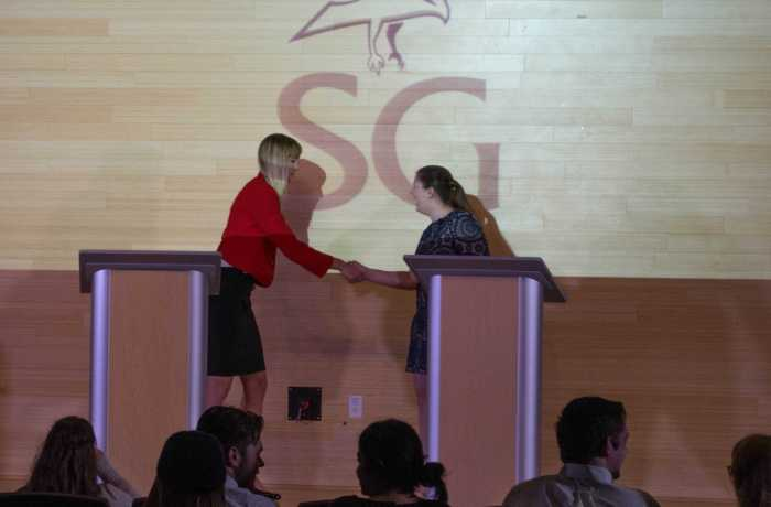 Candidates shake hands at the SG presidential debate. Photo by Lili Weinstein