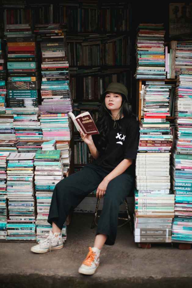 woman sitting near stacks of books and reading