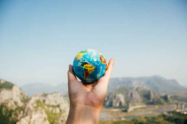 person holding world globe  and taking the benefits of the stoic mind into practice