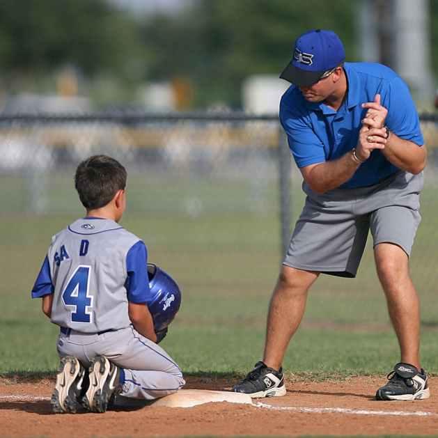 boy in baseball uniform receiving coaching from his coach