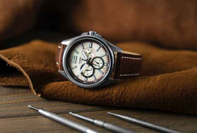 elegant wristwatch with leather strap on table