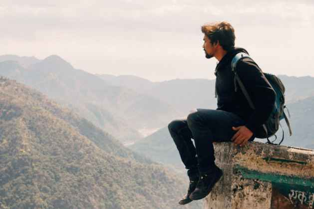 risky traveler sitting and dangling on stone above valley dwelling on removing anxiety from life
