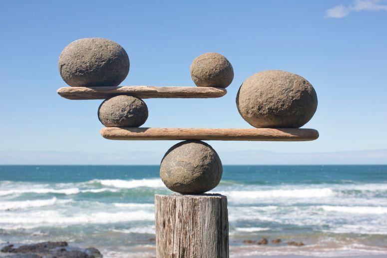 rocks-balancing-on-driftwood--sea-in-background-153081592-591bbc3f5f9b58f4c0b7bb16
