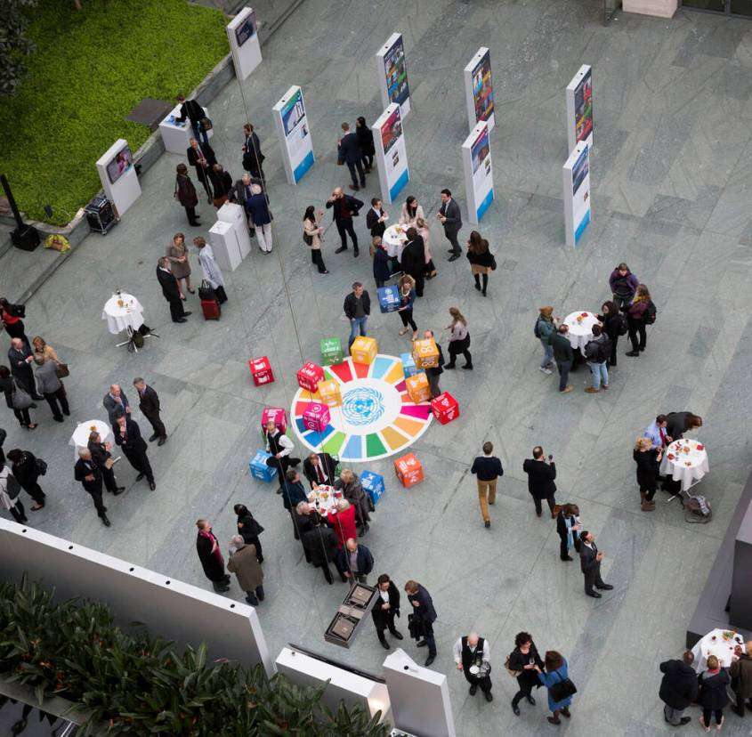 People in an event, gathering around boxes of the Sustainable Development Goals