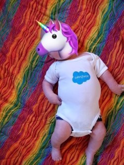 baby in salesforce onesie with unicorn emoji blocking his face.