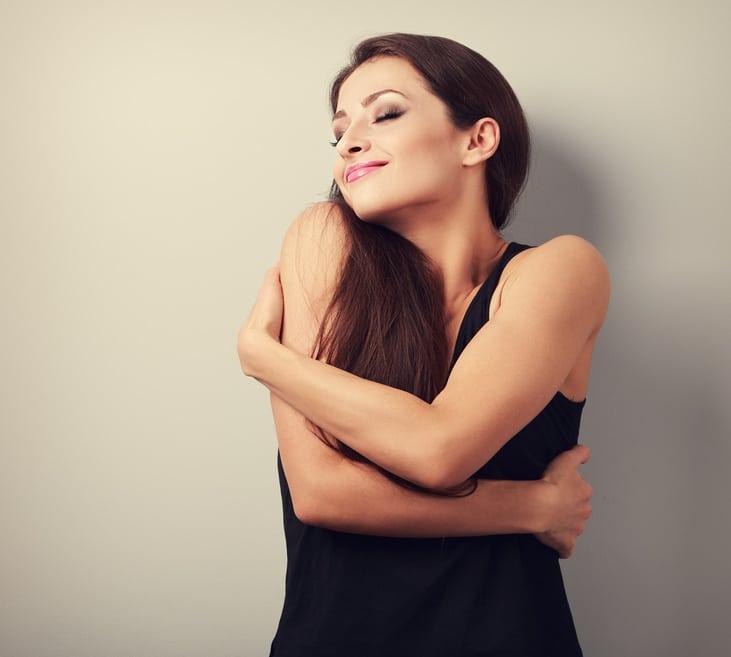 Eine junge Frau mit schwarzen langen Haaren umarmt sich selbst sehr liebevoll und lächelt verträumt dabei mit geschlossenen Augen. Sie zeigt mit ihrer Körperhaltung, dass sie ihr Selbstbewusstsein richtig stärken konnte. Sie ist bekleidet mit einem schwarzem Sommerkleid und der Hintergrund ist einfarbig braun. Das Bild insgesammt sieht sehr elegent aus.