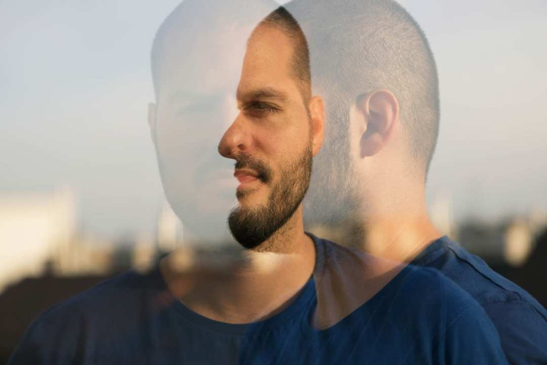 Ein Mann mit kurzen Haaren, zirka 3 Millimeter länge sieht sehr Selbstbewusst in die Ferne. Er hat einen 3 Tages Bart und ist mit einem blauen T-shirt bekleidet. Der Hintergrund ist nicht zu erkennen weil das Bile verschwommen dargestellt ist und der Fokus direkt auf dem Gesicht des mannes liegt.