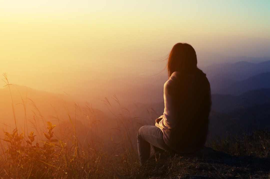 Eine Frau sitzt auf einem Berggipfel und genießt die Ruhe. Dadurch kann sie ihr Selbstvertrauen stärken, indem sie lange Zeit alleine nachdenkt. Im Hintergrund sind viele Berghügel zu sehen, es ist Abendrot mit Nebel.
