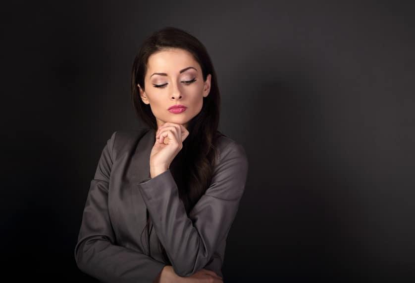 Eine Frau mittleren Alters steht ein nachdenklicher Position und hat Ihren linken arm unter das Kinn gestützt. Sie strahlt mit dieser Gestik und Gesichtsmimik Arroganz und starkes Selbstbewusstsein aus. Sie hat sehr lange, glänzend braune Haare und ist bekleidet mit einer braunen Businessjacke. Der Hintergrund ist ebenfalls schlicht braun.