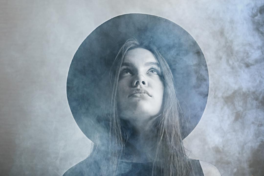 Eine junge Frau mit einem nachdenklichen Gesicht, steht im Nebel und trägt einen Hut. Sie hat lange braune Haare und denkt über ihre Minderwertigkeitskomplexe nach.
