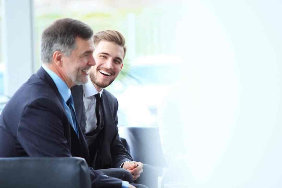 2 männliche Führungskräfte sitzen in einem Büro und lachen ausdrucksstark. Mit ihrer Ausstrahlung zeigen beide ein starkes Selbstbewusstsein, welches sie durch die Programme der unibee Institute zur Persönlichkeitsentwicklung erreicht haben. Beide sind bekleidet mit einem dunkelblauen Anzug, weissen Hemd und blauer Kravatte. Beide Männer haben kurze graue Haare und im Hintergrund ist ein Büro verschwommen zu sehen mit einem großen Bodentiefen Fenster. Weiter steht hinter den beiden Managern eine große grüne Zimmerpalme.