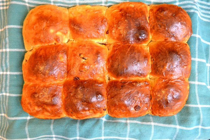 Cranberry Orange Hot Cross Buns after baking on green towel