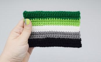 hand holding a crochet aromantic pride flag