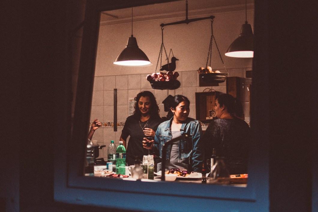 Three friends stand and talk