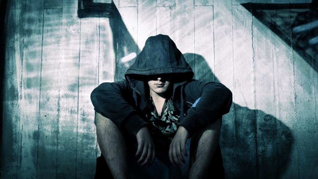Person sits alone in a hoodie