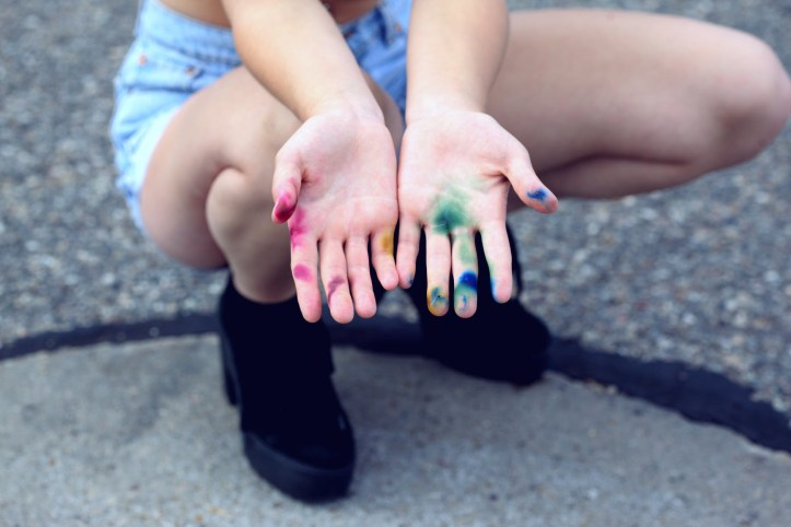 Person kneels with rainbow paint splashes to hands