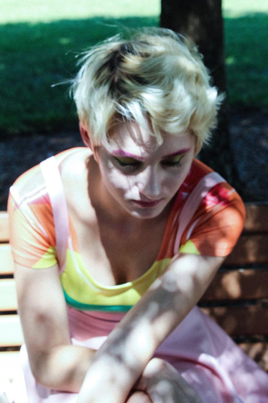 A rainbow shirt woman sits sadly