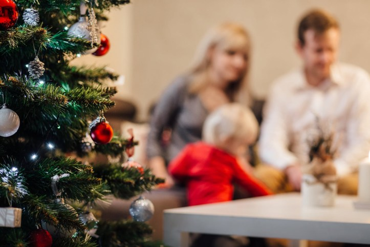 Family in background with Christmas tree