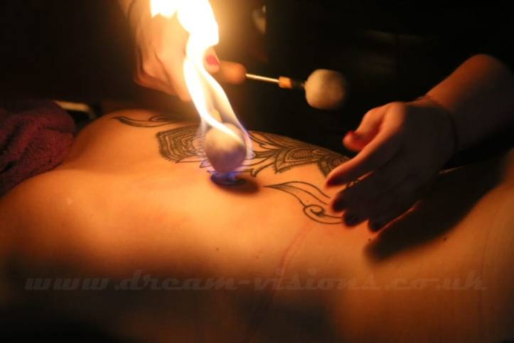 Fire wands on the back of a person with tattoos