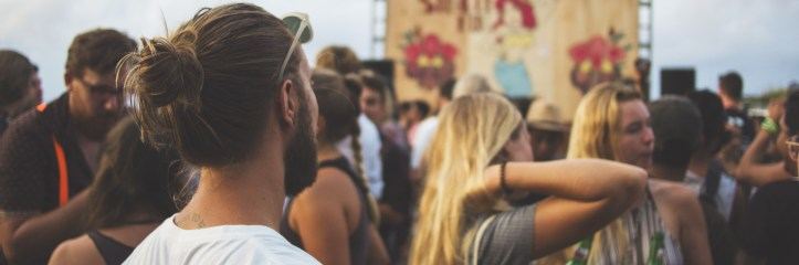 man looks at two women at a concert