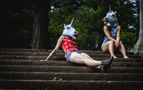 Two women with unicorn heads oon sit on the stairs outside