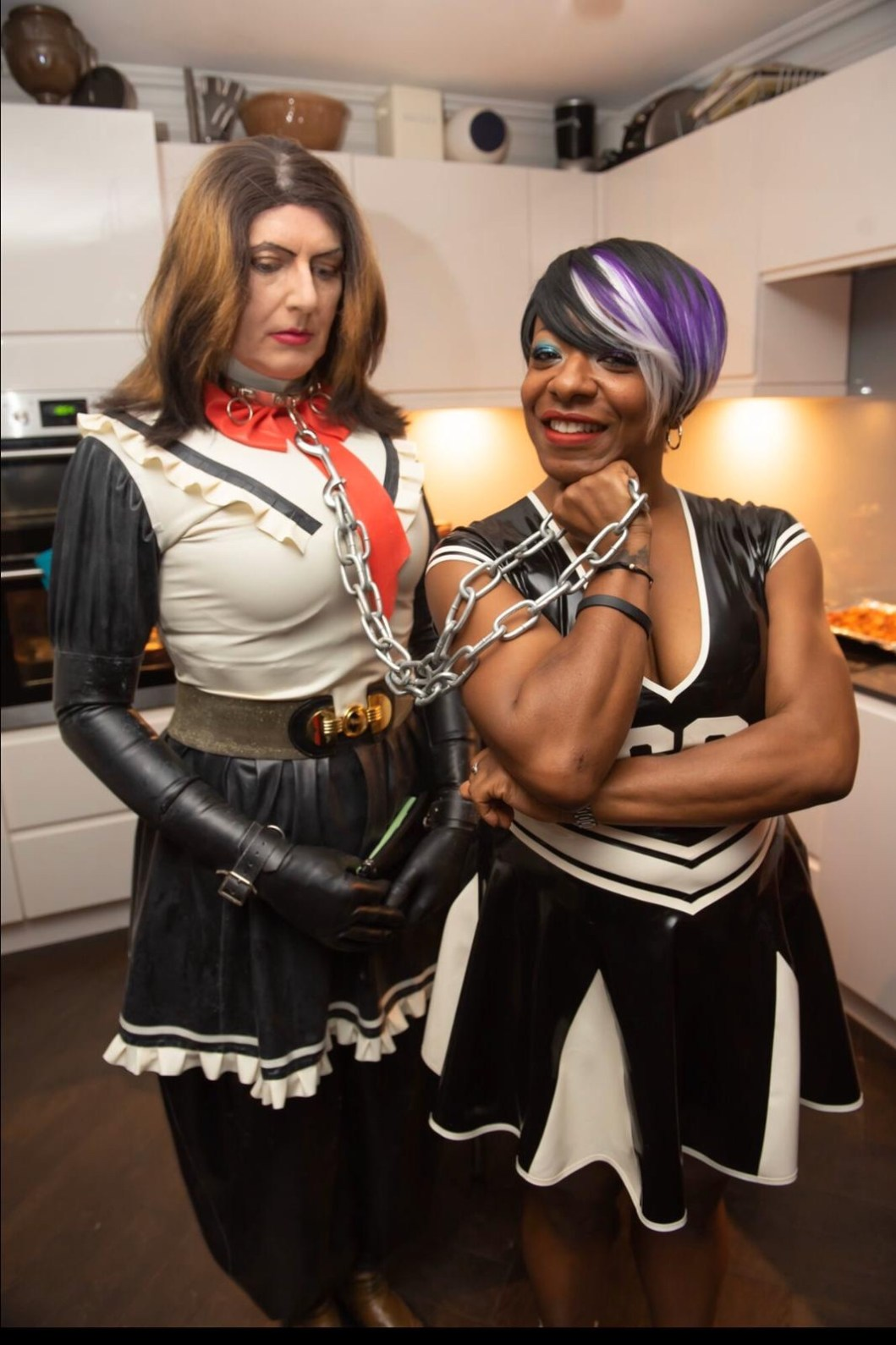 A dark haired woman stands in a rubber dress holding a sissy in rubber by a chain