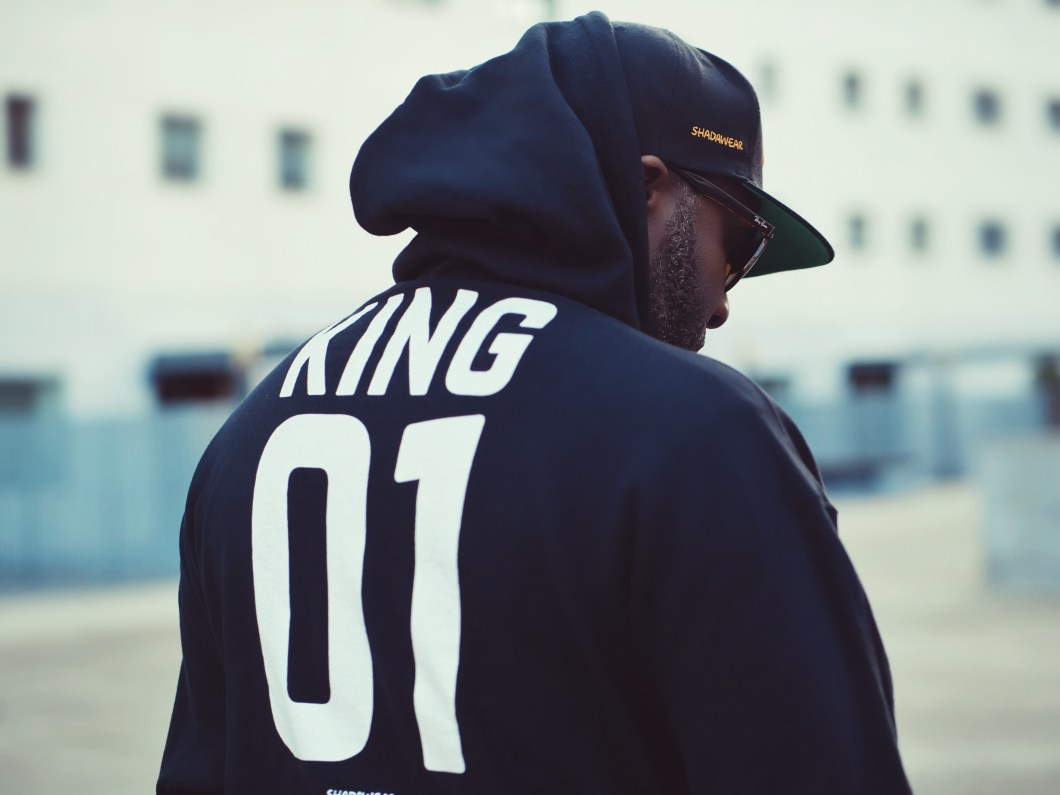 Black man with a beard wears a dark blue hoodie that says King 01 with hat and sunglasses