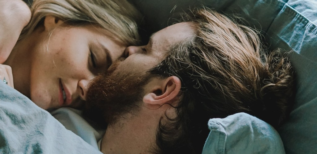 dark haired bearded man kissing blonde woman on the forehead