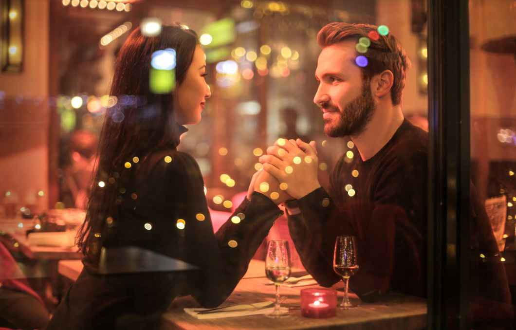 man and woman sit at table with lights and champagne glasses, holding hands