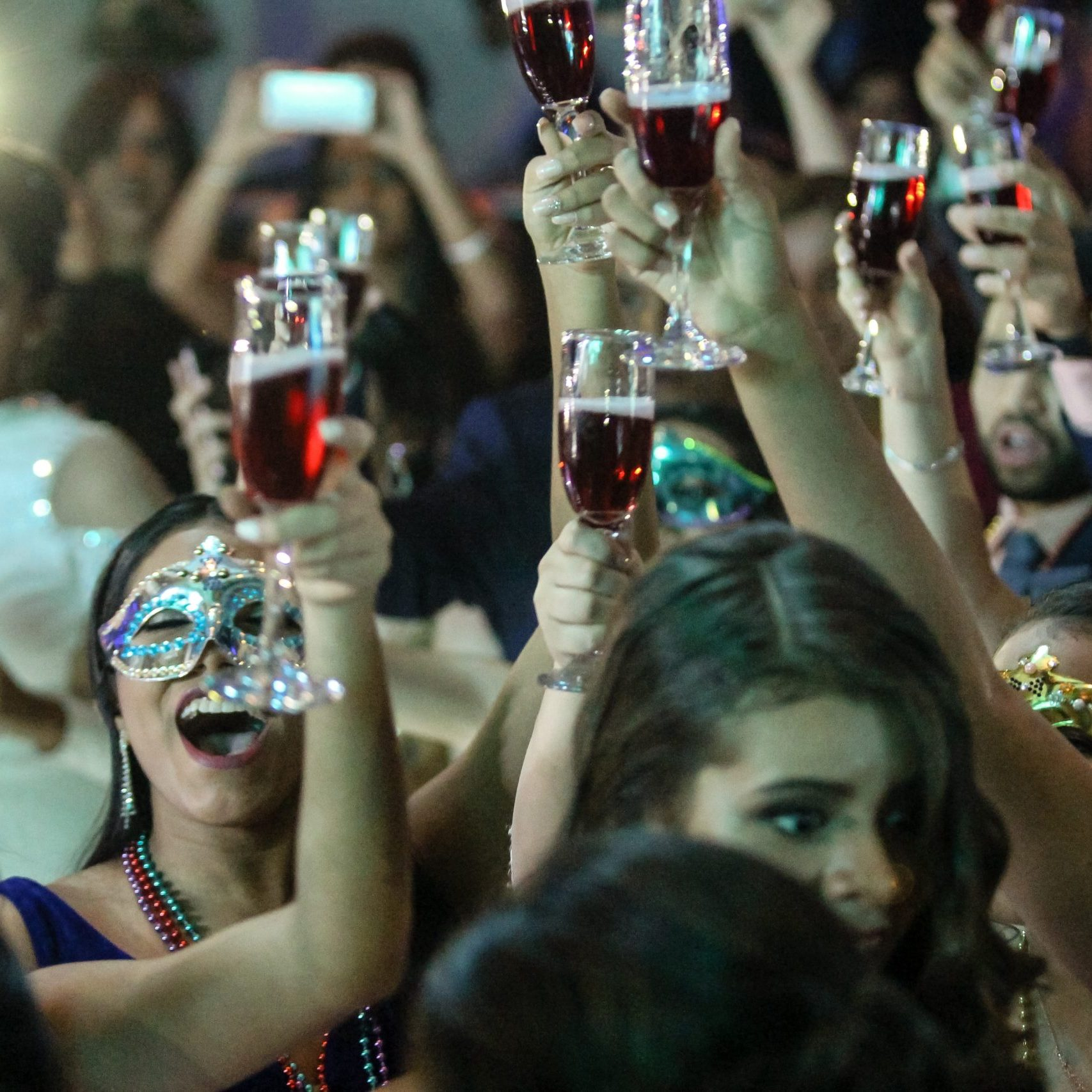 Event reviews category with people in masks at a party with champagne