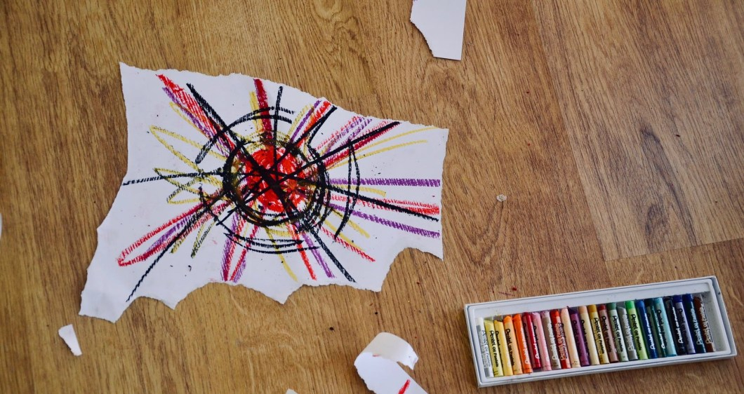 Torn paper with multi coloured drawing and box of coloured crayons on the floor