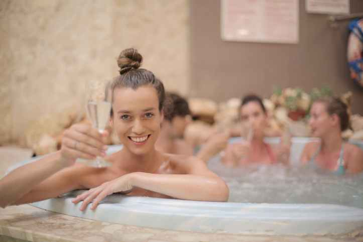 Woman with champagne glass in hot tub.  Not actually taken in Mykonos as they haven't done their first swinger event yet, but could be good lifestyle inspiration