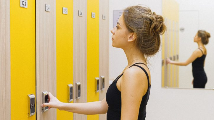 woman in black tank top opening locker.  Her one seems to work.  I had no luck at the gym that day.