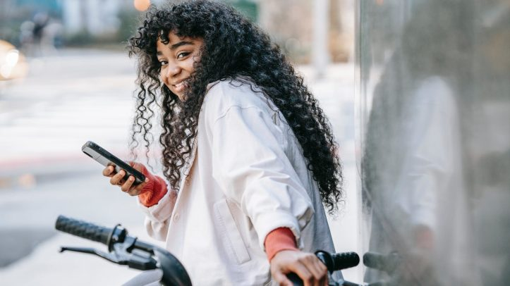 cheerful black woman with bicycle using smartphone on street.  Is her covid vaccine status on her dating app profile?