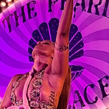 Snake Dancer in Front of Pearl Necklace stage sign, arms up