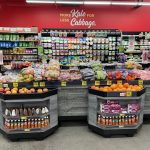 Grocery Outlet Bargain Markets In-Store Orchard Bins With Apples And Oranges Sitting On Top Of Display Bin Shelving With More Kale For Less Cabbage In Background On Red Wall