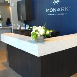 Universal Custom Display UCD Commercial L Shaped White Marble Reception Desk With White Flowers In Front And Blue Wall Background With Word Monark Premium Appliance Co