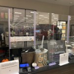 Universal Custom Display UCD PPE Clear Plastic Partition Barrier On Top Of Cashier Counter Desktop In Starbucks Coffee Shop