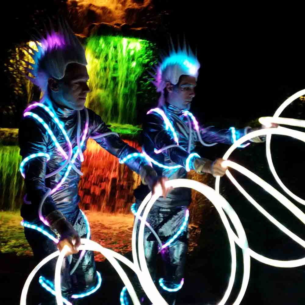 Two Lit Up Costumed Characters Holding Glowing Hoops