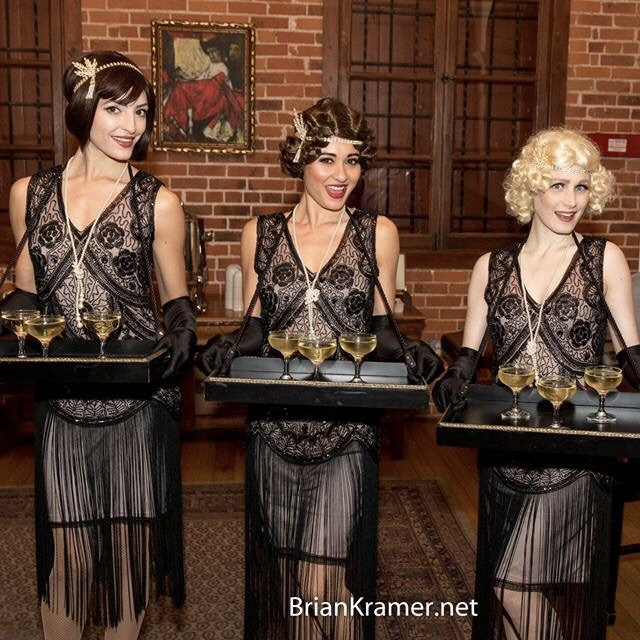 Three ladies serve champagne.