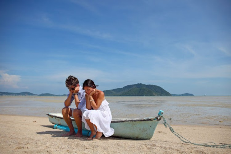 Sad couple sitting on old boat on tropical beach