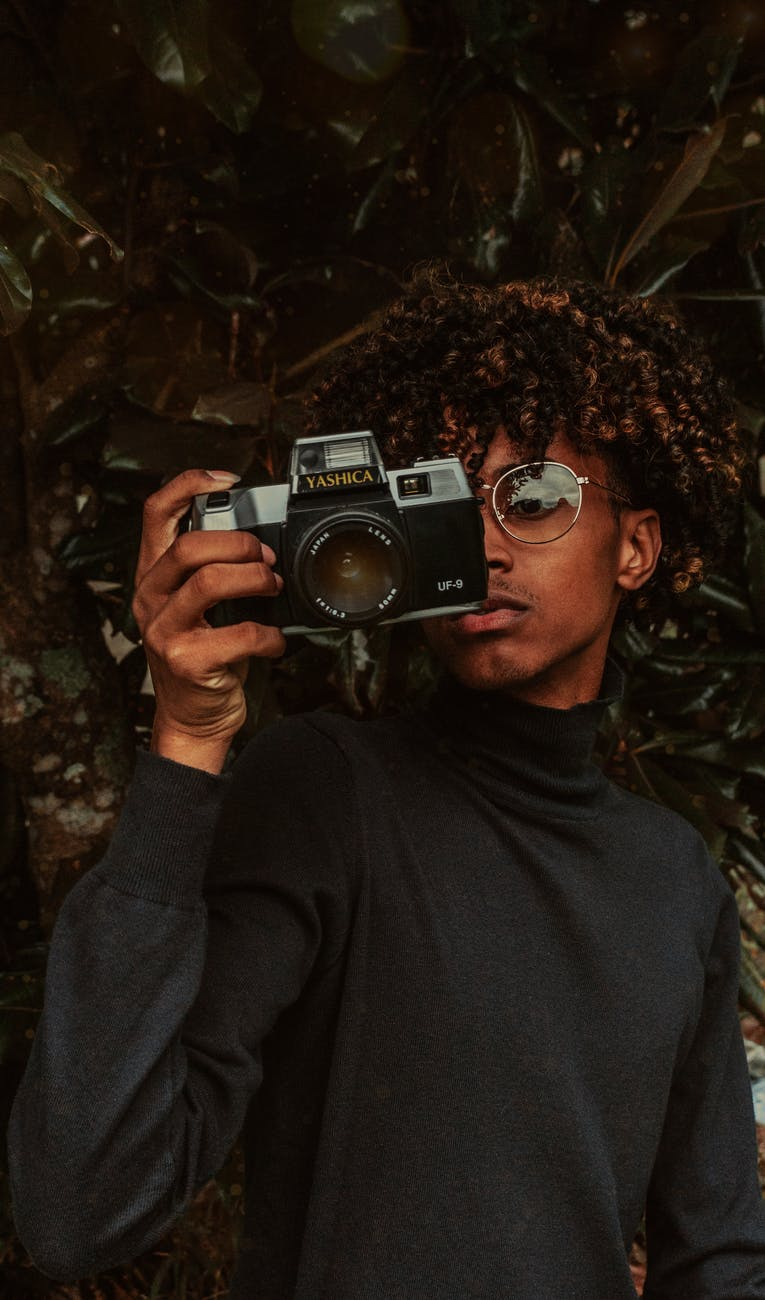 focused black teenager using vintage photo camera in garden