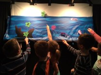 Backstage view, moving shadow puppets underwater scene at Digby Elementary