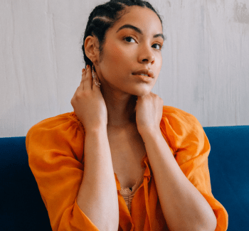 Devri Velazquez sits wide her hands framing her face. She wears an orange peasant top on a background of smooth cement walls and a teal velvet banquette. Her hair is braided and pulled away from her face, and she wears eyeshadow that complements the color of her top.