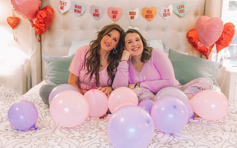 Jaelin and Natalie Palmer sit in a plush pink bed with Valentine's love hearts strung on a banner behind them. In the foreground are lavender and light pink balloons, as well as some red and pink balloons in the back corners of the frame. Both rest on light green pillows an wear pink tops, smiling.